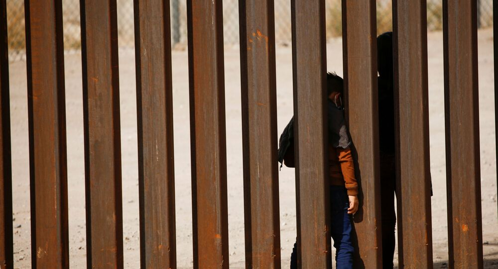 Migrant child is seen through the border wall after crossing the Rio Bravo river to turn himself with his family in to U.S. Border Patrol agents to request for asylum in El Paso, Texas, U.S., as seen from Ciudad Juarez, Mexico March 29, 2021