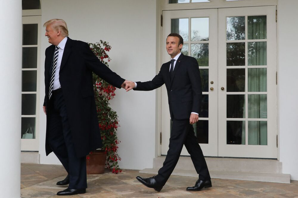 French President Emmanuel Macron (R) and then US President Donald Trump (R) walk hand in hand under the colonnades of the White House in Washington, DC, on 24 April 2018.