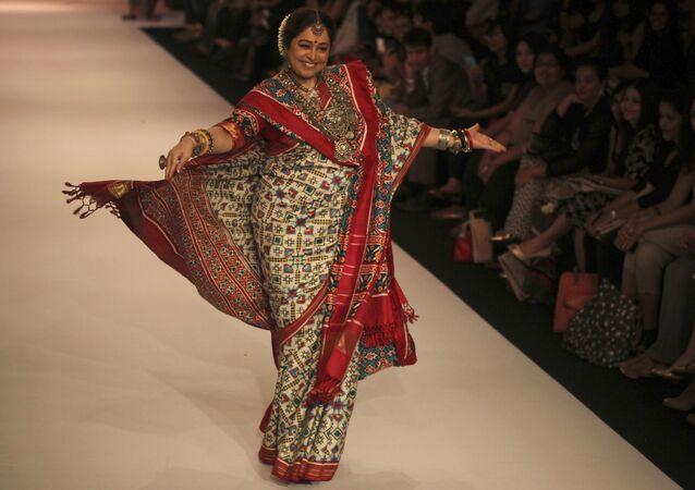Indian actress Kirron Kher displays a creation by Gaurang at the Lakme Fashion Week in Mumbai, India, Monday, Aug. 26, 2013