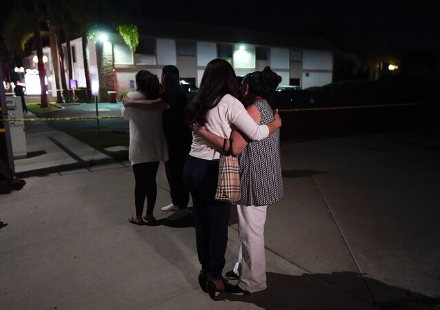 Unidentified people comfort each other as they stand near a business building where a shooting occurred in Orange, Calif., Wednesday, March 31, 2021
