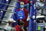In this March 21, 2021, file photo, an usher holds a sign reminding fans to wear masks during a college basketball game between Houston and Rutgers in the second round of the NCAA tournament at Lucas Oil Stadium in Indianapolis