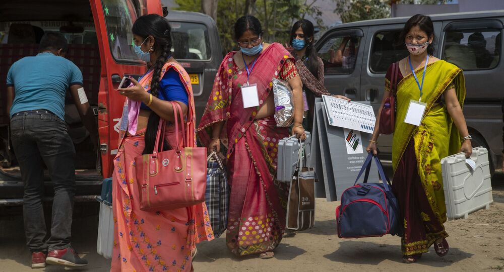 Election officers carry Electronic Voting Machines (EVM) as they leave for their respective polling stations on the eve of the Assam Assembly election in Majuli, India, Friday, March 26, 2021
