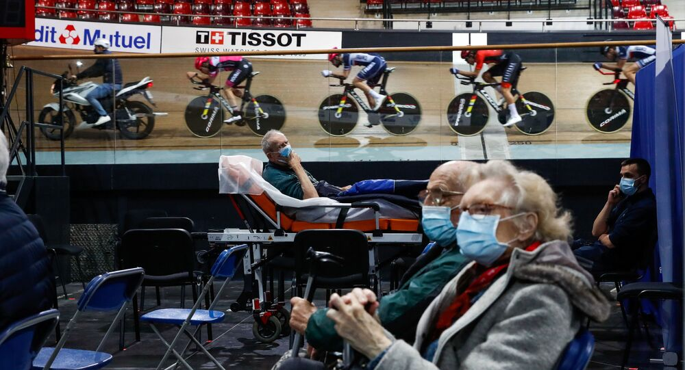 France's national cycling team trains as people wait to get a dose of the Comirnaty Pfizer-BioNTech COVID-19 vaccine as part of the coronavirus disease vaccination campaign at the indoor Velodrome National of Saint-Quentin-en-Yvelines in Montigny-le-Bretonneux, southwest of Paris, France, March 26, 2021