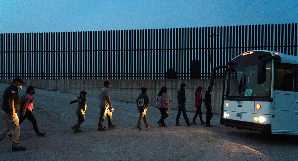 Asylum-seeking migrants' families queue to board a bus as they wait to be transported by the U.S. Border Patrols after crossing the Rio Grande river into the United States from Mexico in Penitas, Texas, U.S., March 26, 2021.