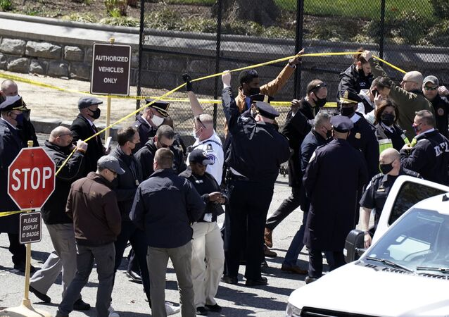 Police officers gather near a car that crashed into a barrier on Capitol Hill in Washington, Friday, April 2, 2021.