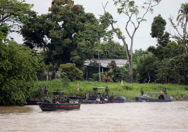 Venezuelan soldiers patrol by boat on the Arauca River, the border between Colombia and Venezuela, as seen from Arauquita, Colombia, March 28, 2021.