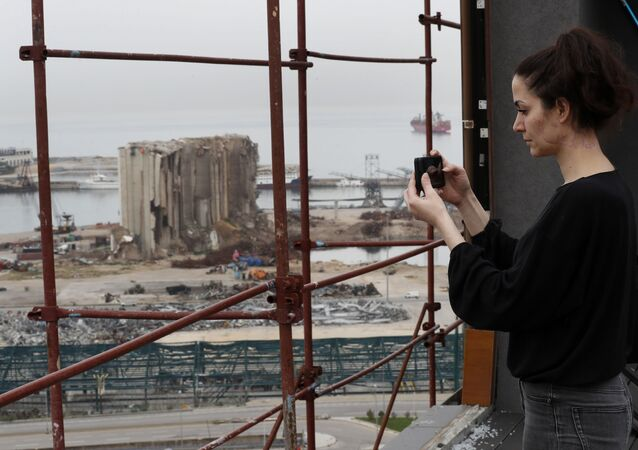 Joana Dagher, 33, who lost her memory for two full months from the trauma she suffered in the massive August explosion at the Beirut port, including a cerebral contusion and brain lesions, takes pictures of the explosion scene from her damaged apartment rooftop, in Beirut, Lebanon, Wednesday, Jan. 27, 2021.