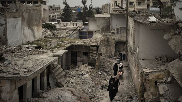 In this March 12, 2020 file photo, women walk in a neighborhood heavily damaged by airstrikes in Idlib, Syria. - Sputnik International