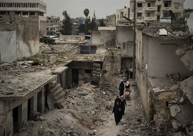 In this March 12, 2020 file photo, women walk in a neighborhood heavily damaged by airstrikes in Idlib, Syria.