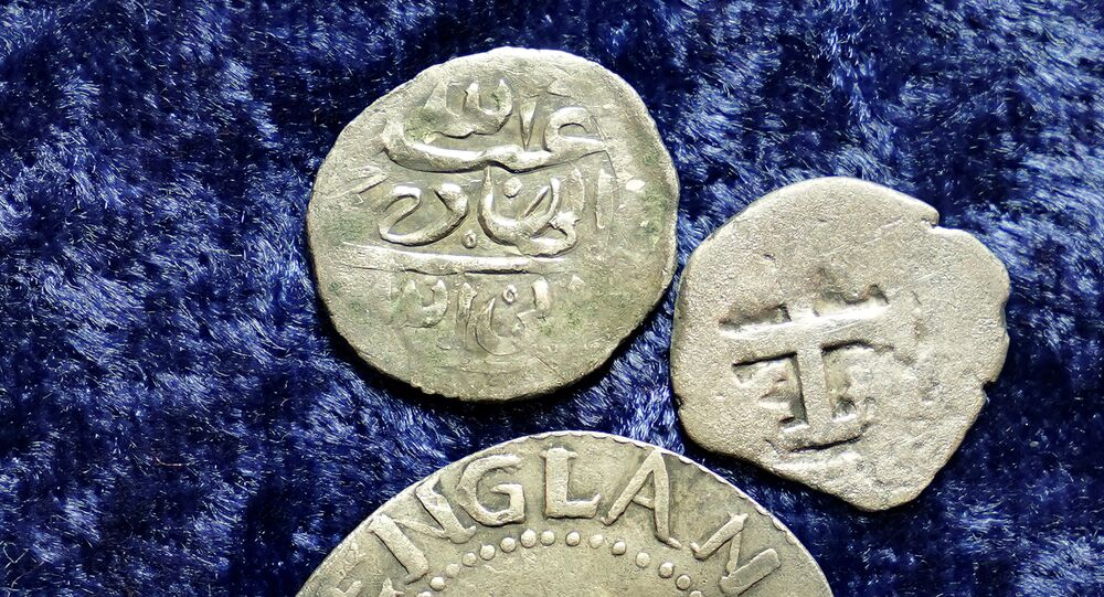 A 17th century Arabian silver coin, top, that research shows was struck in 1693 in Yemen, rests near an Oak Tree Shilling minted in 1652 by the Massachusetts Bay Colony, below, and a Spanish half real coin from 1727, right, on a table, in Warwick, R.I., Thursday, March 11, 2021.
