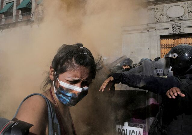 A woman reacts as she clashes with police officers during a protest in support of Victoria Salazar, a Salvadoran woman who died after a Mexican female police officer was seen in a video kneeling on her back, in Mexico City, Mexico April 2, 2021.