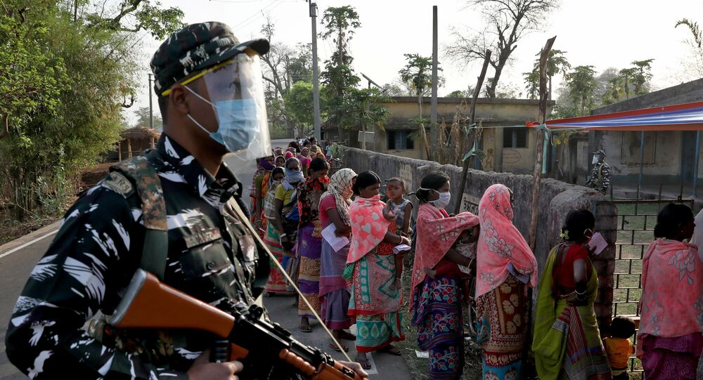 An armed policeman wearing a face shield stands guard as women wait in line to cast their votes outside a polling booth during the first phase of the West Bengal state election in Purulia district, India, March 27, 2021.