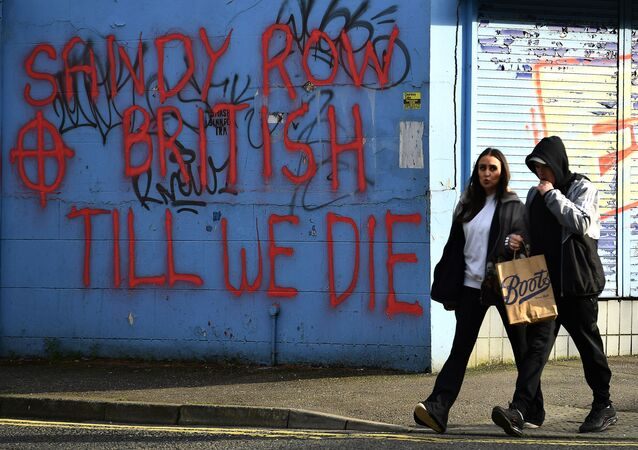 People walk past graffiti saying 'Sandy Row, British till we die' in Belfast, Northern Ireland, March 6, 2021. Picture taken March 6, 2021. REUTERS/Clodagh Kilcoyne