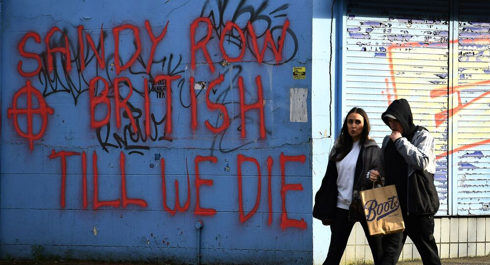 People walk past graffiti saying 'Sandy Row, British till we die' in Belfast, Northern Ireland, March 6, 2021. Picture taken March 6, 2021. REUTERS/Clodagh Kilcoyne