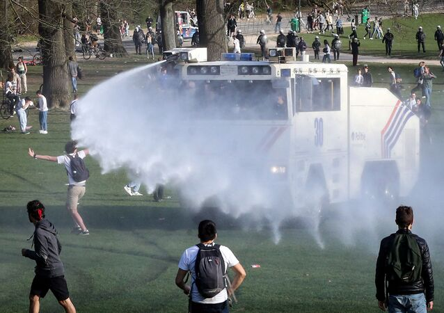 Bystanders and demonstrators are soaked by a Belgian police water canon as law enforcement officers surround them at Bois de la Cambre, in Brussels, on 1 April 2021 during an unauthorised rally and fake concert announced on social media as an April Fool's Day prank. (Photo by Franзois WALSCHAERTS / AFP) (Photo by Franзois WALSCHAERTS / AFP)