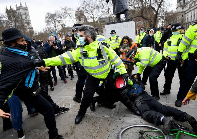 Police officers restrain demonstrators during a protest in London, Britain, April 3, 2021. REUTERS/Toby Melville