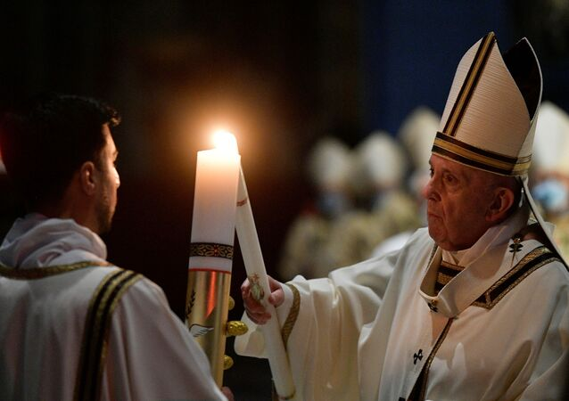 Pope Francis celebrates the Easter Vigil in a near empty St. Peter's Basilica as the coronavirus disease (COVID-19) restrictions stay in place for a second year running, at the Vatican, April 3, 2021.