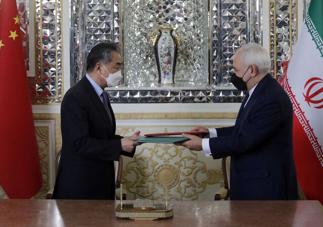 Iranian Foreign Minister Mohammad Javad Zarif (R) and his Chinese counterpart Wang Yi, are pictured during the signing of an agreement in the capital Tehran, on March 27, 2021.