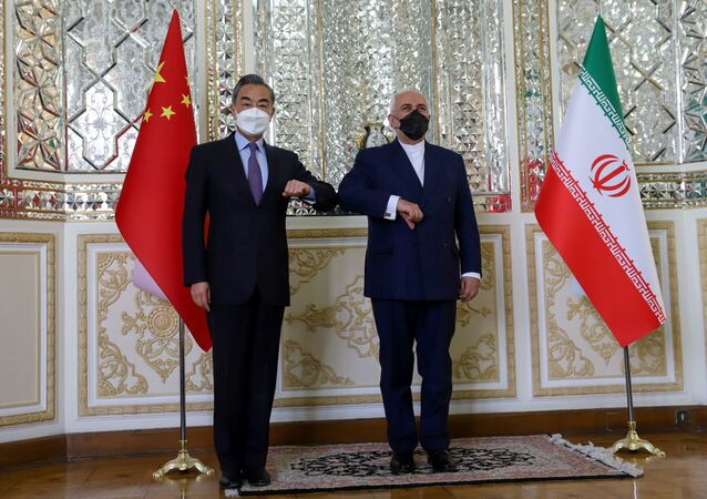 Iran's Foreign Minister Mohammad Javad Zarif and China's Foreign Minister Wang Yi bump elbows during the signing ceremony of a 25-year cooperation agreement, in Tehran, Iran March 27, 2021.