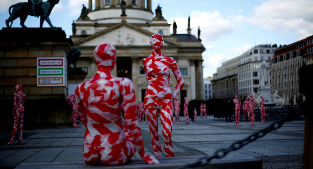 Mannequins wrapped in red and white barricade tape to symbolize the coronavirus disease crisis are placed at the Gendarmenmarkt square as part of a COVID-19 art installation It is like it is by German artist Dennis Josef Meseg in Berlin, Germany, April 3, 2021.