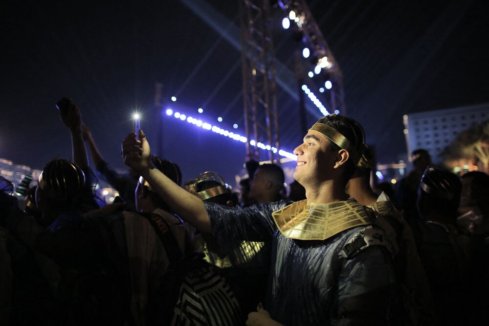 A performer dressed in an ancient Egyptian costume uses his phone to take a selfie photo after the end of the parade of 22 ancient Egyptian royal mummies from the Egyptian Museum in Cairo's Tahrir Square on 3 April 2021, headed to their new resting place at the new National Museum of Egyptian Civilisation (NMEC) about seven kilometres south in historic Fustat (Old Cairo).
