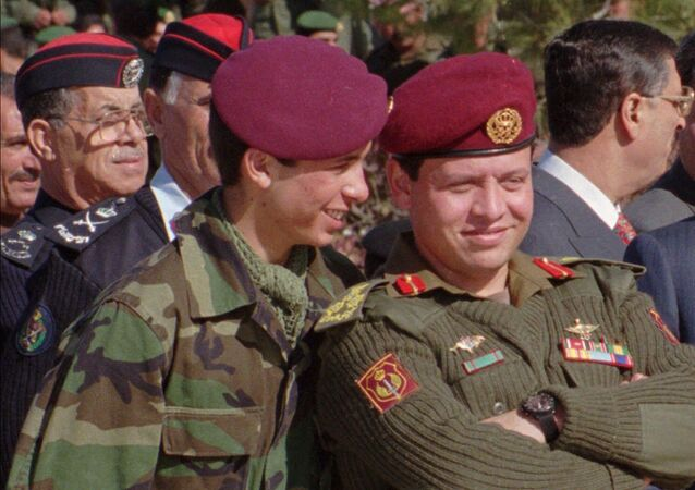 Jordan's Prince Hamza, 19, left, whispers in the ears of his elder brother, Prince Abdullah, 37, in this June 1998 photo taken during a military parade in Jordan.