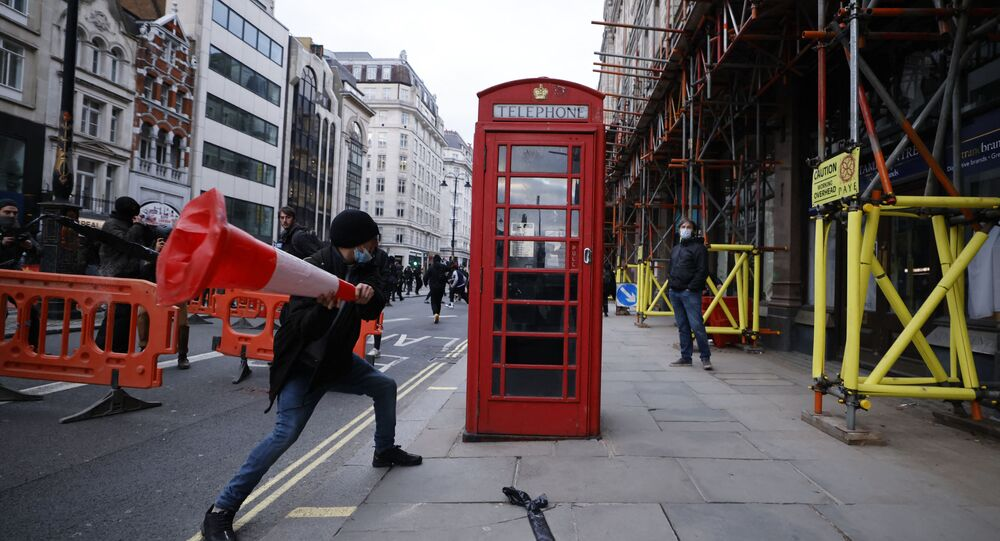 A demonstrator hits a telephone box with a road cone during a 'Kill The Bill' protest against the Government's Police, Crime, Sentencing and Courts Bill in central London on April 3, 2021.