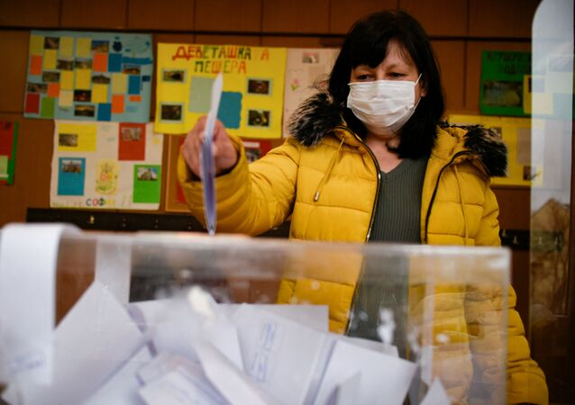 A woman casts her vote at a polling station during the country's parliamentary election in Sofia on April 4, 2021.