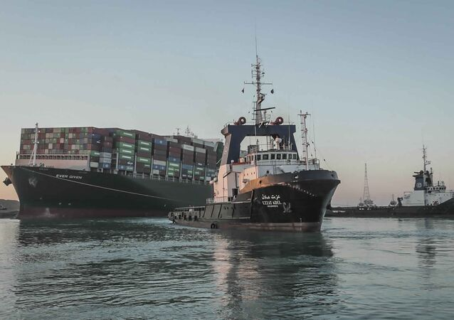 In this photo released by Suez Canal Authority, the Ever Given, a Panama-flagged cargo ship is pulled by one of the Suez Canal tugboats, in the Suez Canal, Egypt, Monday, March 29, 2021