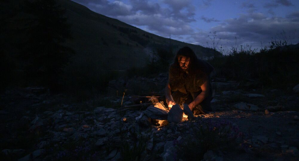 Guido Camia dressed as a Neanderthal Cave man lights a campfire in Chianale, in the Italian Alps, near the French border, on August 7, 2019.