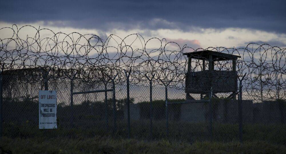 In this photo reviewed by U.S. military officials, the sun sets behind the closed Camp X-Ray detention facility, Wednesday, April 17, 2019, in Guantanamo Bay Naval Base, Cuba.