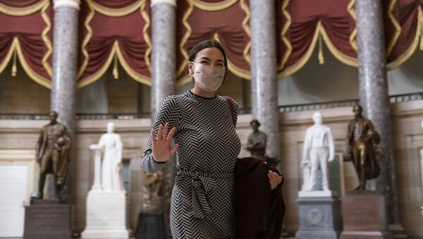 Rep. Alexandria Ocasio-Cortez, D-N.Y., waves to photographers as she walks through Statuary Hall before the vote on the Democrat's $1.9 trillion COVID-19 relief bill, on Capitol Hill, Wednesday, March 10, 2021, in Washington. - Sputnik International