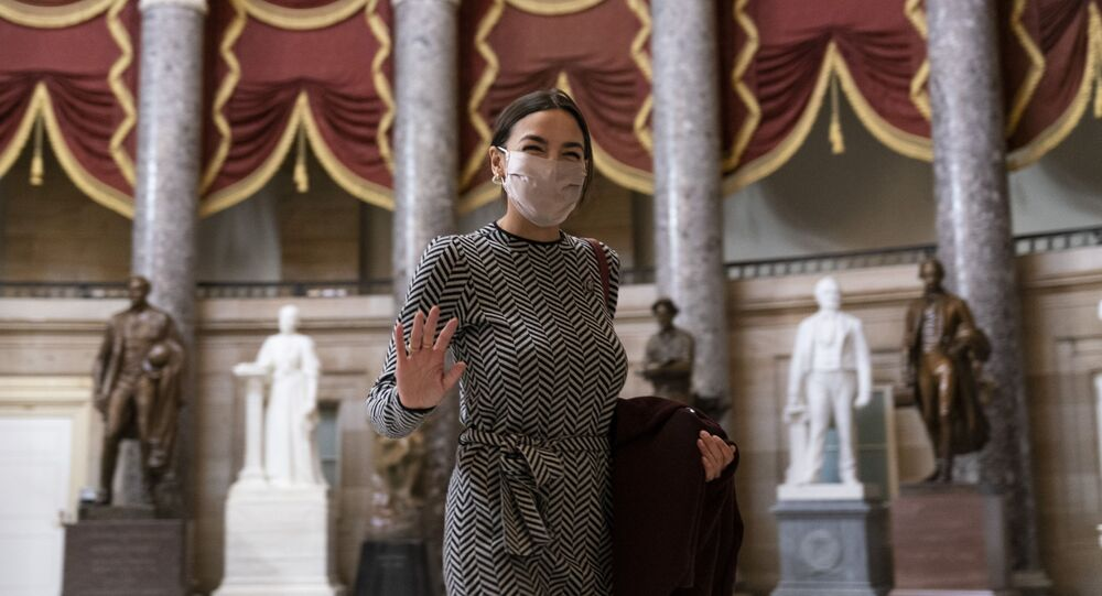 Rep. Alexandria Ocasio-Cortez, D-N.Y., waves to photographers as she walks through Statuary Hall before the vote on the Democrat's $1.9 trillion COVID-19 relief bill, on Capitol Hill, Wednesday, March 10, 2021, in Washington.