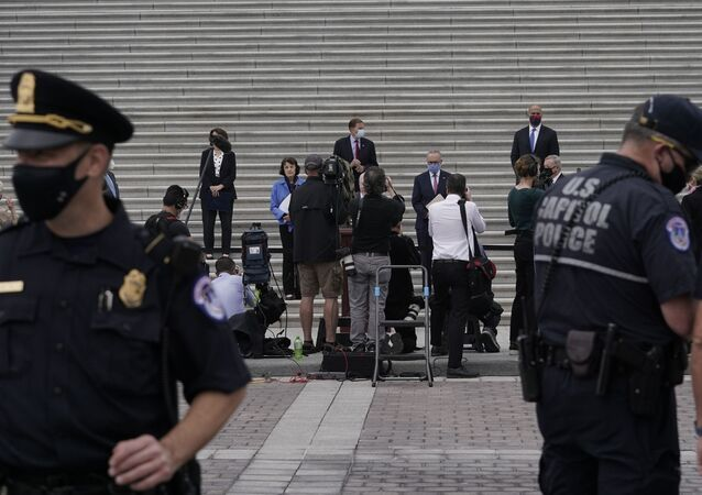 US Capitol Police stand between protesters and Senate Minority Leader Chuck Schumer, D-N.Y., and Democratic members of the Senate Judiciary Committee during a news conference after boycotting the vote by the Republican-led panel to advance the nomination of Judge Amy Coney Barrett to sit on the Supreme Court, Thursday, Oct. 22, 2020, in Washington.