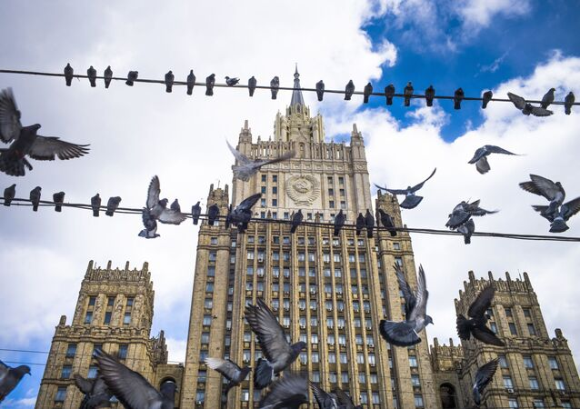 Pigeons take off from wires in front of the Russian Foreign Ministry building, in Moscow, Russia, Thursday, March 29, 2018.