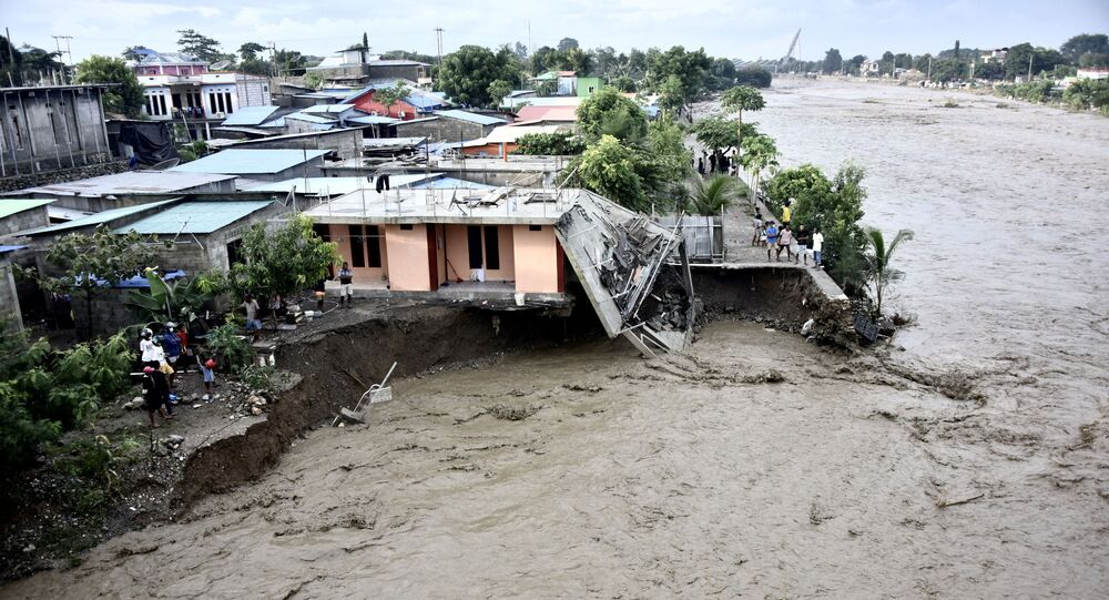 Residents stand along the water's edge by damaged homes after heavy rains and strong winds lashed East Timor's capital Dili overnight causing extensive flooding on April 4, 2021