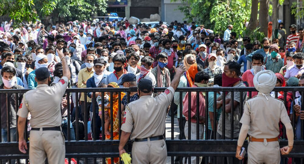 Police personnel stand guard as stranded migrant workers and their families wait to get thermally screened behind the gate of the Guru Nanak Auditorium before going to a railway station to take a train to Bhagalpur in Bihar state back to their hometowns after the government eased a nationwide lockdown imposed as a preventive measure against the COVID-19 coronavirus, in Amritsar on May 17, 2020.