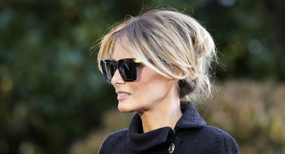 First Lady Melania Trump listens as President Donald Trump speaks with reporters as he walks to board Marine One on the South Lawn of the White House, Wednesday, Jan. 20, 2021, in Washington