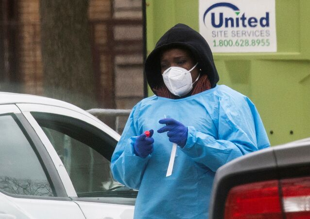 A health worker prepares to do a coronavirus disease (COVID-19) test as people wait at a drive-through COVID-19 testing center in a local street, in Newark, New Jersey, U.S