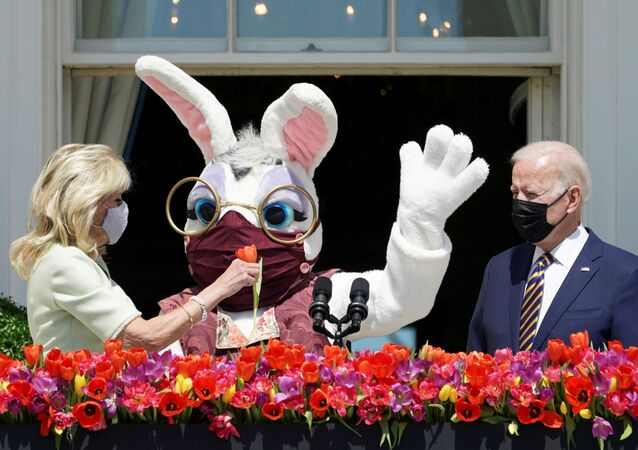 U.S. President Joe Biden stands to deliver his remarks on the tradition of Easter, next to first lady Jill Biden holding a flower and a person wearing an Easter Bunny costume  at the Blue Room Balcony of the White House in Washington, U.S. April 5, 2021.
