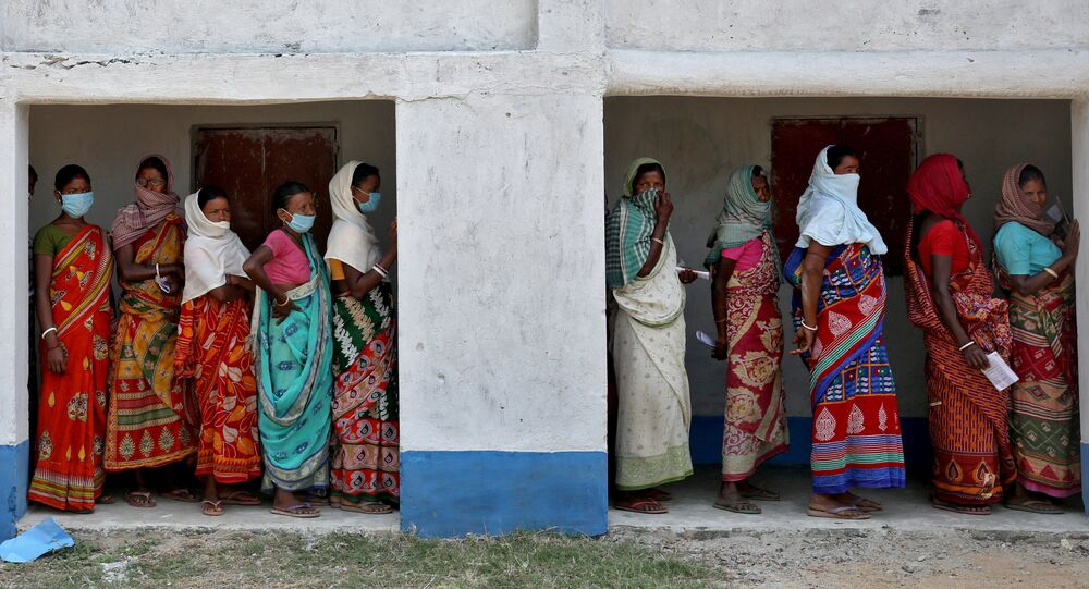 Women wait in line to cast their vote at a polling booth during the first phase of West Bengal state election in the Purulia district, India.