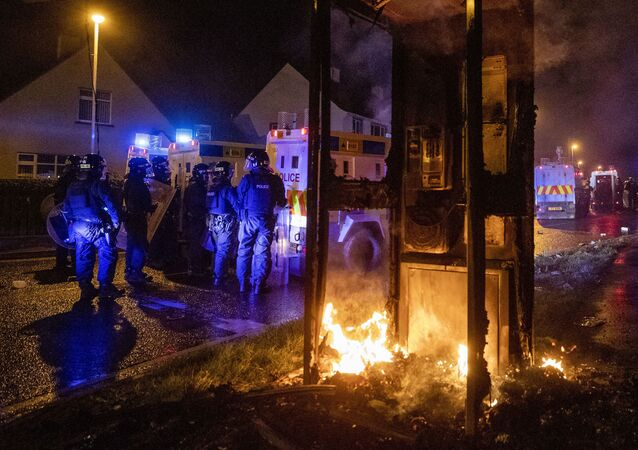 Tactical Support Group (TSG) officers man a burning site close to the Loyalist Nelson Drive Estate in the Waterside area of Londonderry in Northern Ireland, Monday, 5 April 2021
