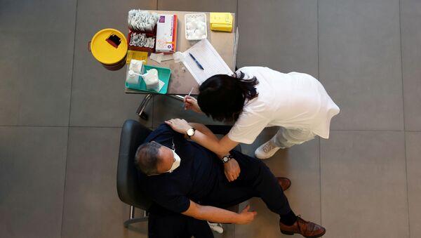 A medical worker vaccinates a man against the coronavirus disease (COVID-19) as Israel kicks off a coronavirus vaccination drive, at Tel Aviv Sourasky Medical Center (Ichilov Hospital) in Tel Aviv, Israel December 20, 2020 - Sputnik International