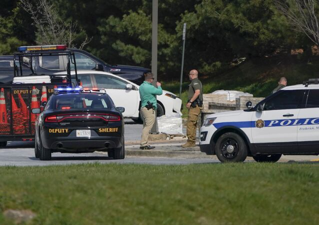 Police talk near the scene of a shooting at a business park in Frederick, Md., Tuesday, April 6, 2021.