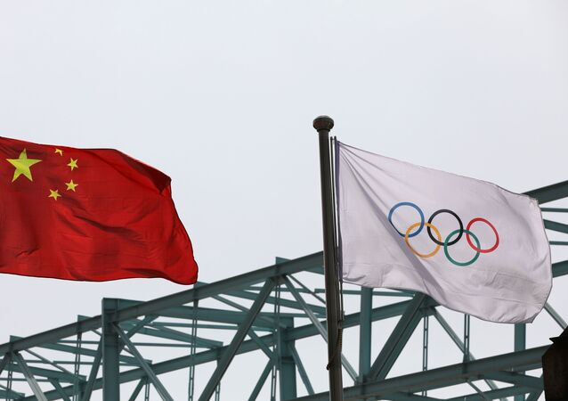 A Chinese national flag flutters next to an Olympic flag at the Beijing Organising Committee for the 2022 Olympic and Paralympic Winter Games, in Beijing, China March 30, 2021