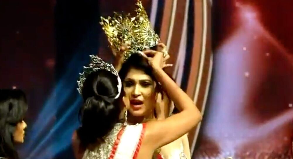 "Screenshot captures the moment Mrs World 2020 Catherine Jurie snatches the crown away from Pushpika De Silva, the 2021 winner of the ""Mrs Sri Lanka"" beauty contest, over claims that she did not qualify for the contest because she is divorced."