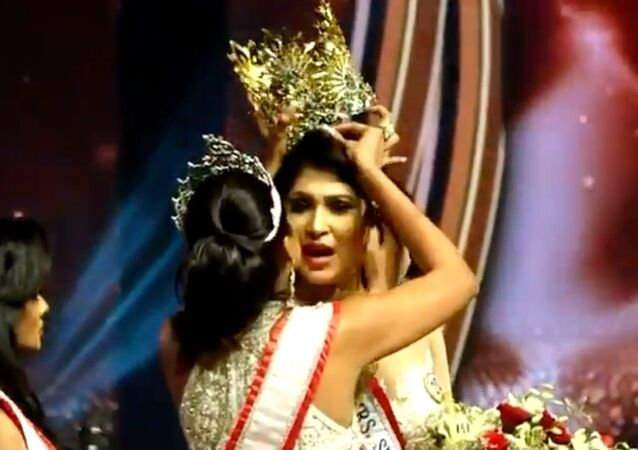 "Screenshot captures the moment that Mrs World 2020 Catherine Jurie snatches the crown away from Pushpika De Silva, the 2021 winner of the ""Mrs Sri Lanka"" beauty contest, over claims that did not qualify for the contest on the grounds that she was divorced."