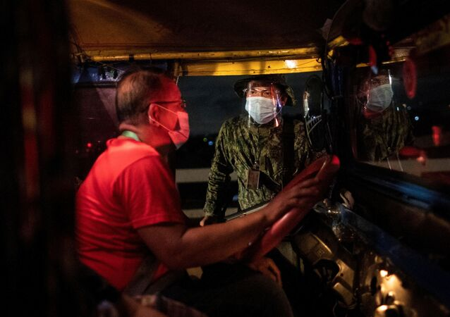 An armed policeman talks to a jeepney driver at a checkpoint placed to implement a curfew in the country's capital amid rising coronavirus disease (COVID-19) infections, in Quezon City, Metro Manila, Philippines, March 15, 2021.