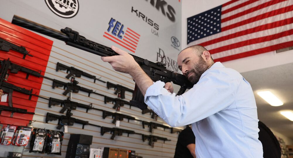 """Austin Title handles a weapon as he visits WEX Gunworks on March 24, 2021 in Delray Beach, Florida. U.S. President Joe Biden has called on lawmakers to """"immediately pass"""" legislation to help curb gun violence in the county."""