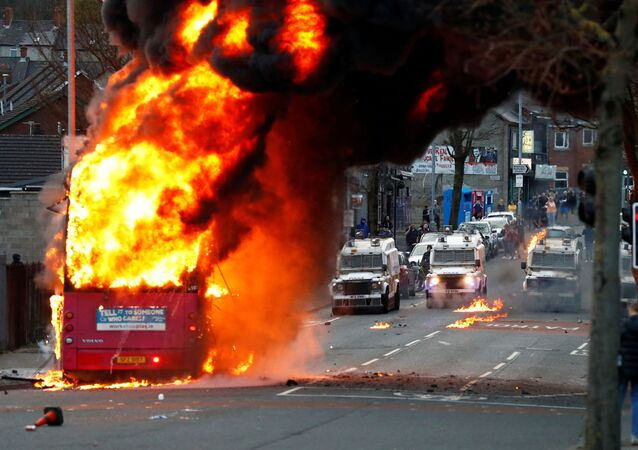Police vehicles are seen behind a hijacked bus burns on the Shankill Road as protests continue in Belfast, Northern Ireland, 7 April 2021